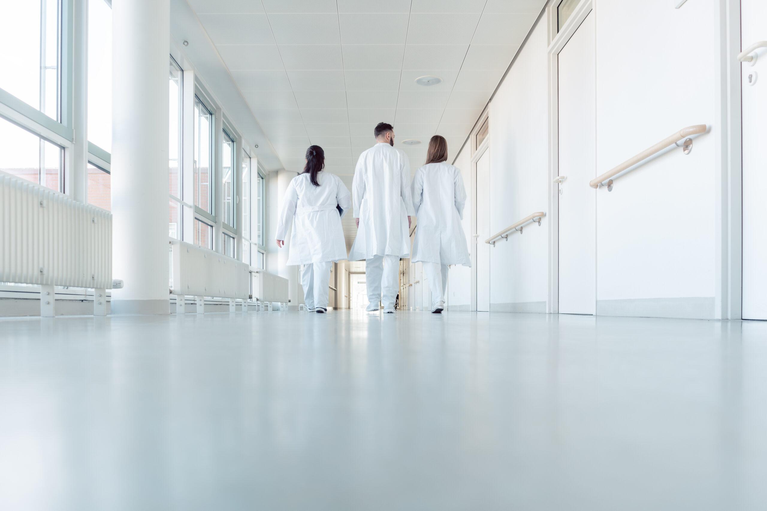 Doctors walk through white corridor together