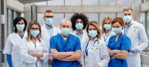 Team of D.med Doctors and Nurses standing together with PPE masks.